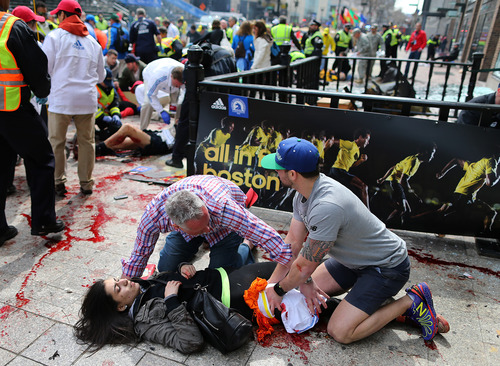 An injured woman is tended to at the finish line of the Boston Marathon,  in Boston, Monday, April 15, 2013. Two explosions shattered the euphoria of the Boston Marathon finish line on Monday, sending authorities out on the course to carry off the injured while the stragglers were rerouted away from the smoking site of the blasts. (AP Photo/The Boston Globe,  John Tlumacki) MANDATORY CREDIT; BOSTON OUT