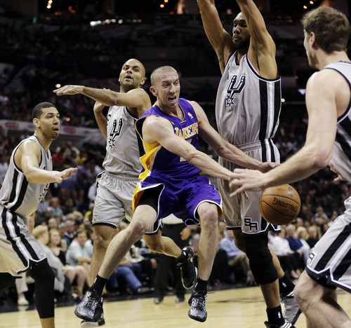 Los Angeles Lakers' Steve Blake, center, is surrounded by San Antonio Spurs', from left, Danny Green, Tony Parker, Tim Duncan and Tiago Splitter as he tries to drive to the basket during the first half of Game 1 of their first-round NBA playoff basketball series, Sunday, April 21, 2013, in San Antonio. (AP Photo/Eric Gay)