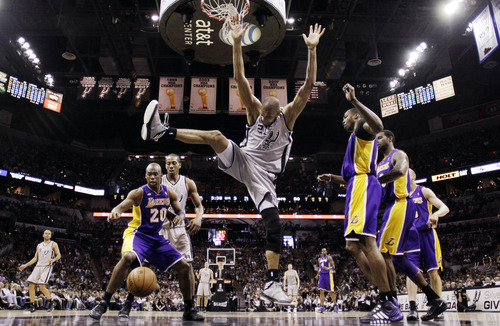 San Antonio Spurs' Tim Duncan, center, is stripped of the ball as Los Angeles Lakers' Jodie Meeks (20) looks to gain possession during the second half of Game 1 of their first-round NBA basketball playoff series, Sunday, April 21, 2013, in San Antonio. San Antonio won 91-79. (AP Photo/Eric Gay)