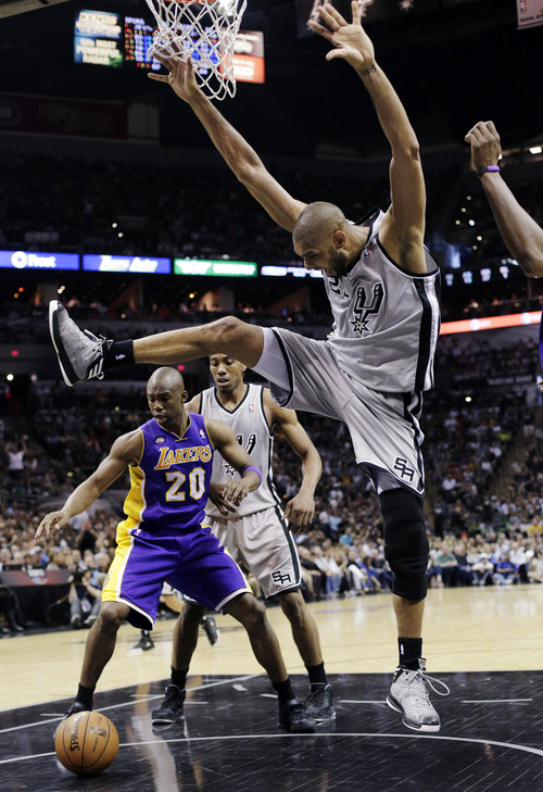 San Antonio Spurs' Tim Duncan (21) is stripped of the ball as Los Angeles Lakers' Jodie Meeks (20) looks to gain possession during the second half of Game 1 of their first-round NBA basketball playoff series, Sunday, April 21, 2013, in San Antonio. San Antonio won 91-79. (AP Photo/Eric Gay)
