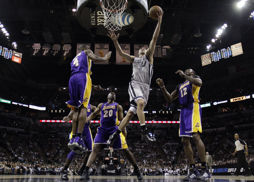 San Antonio Spurs' Manu Ginobili, front center, of Argentina, drives to the basket between Los Angeles Lakers' Antawn Jamison (4), Jodie Meeks (20) and Dwight Howard (12) during the second half of Game 1 of their first-round NBA basketball playoff series on Sunday, April 21, 2013, in San Antonio. San Antonio won 91-79. (AP Photo/Eric Gay)