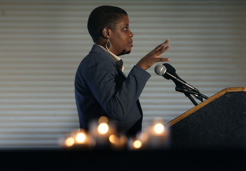 Scott Sommerdorf  |  The Salt Lake Tribune With candles from an earlier remembrance ceremony burning in the foreground, Consolee Nishimwe speaks about the atrocities she escaped during Rwanda's genocide, Sunday, April 21, 2013. For the third year, survivors of the Tutsi genocide in Rwanda living in Utah gathered to commemorate the event. There are about 50 Tutsi in Utah, according to the Never Again Association, which is sponsoring the event.