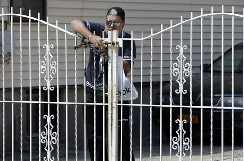 "An unidentified man locks a gatein West New York, N.J., Monday, April 22, 2013, alongside the apartment of Ailina Tsarnaev, a sister of the Boston Marathon bombing suspects. Attorney Joseph Ginarte said Tsarnaev, 22, plans to release a statement, possibly on Tuesday. Ginarte says it's a very difficult time for the family and ""you can imagine what they are going through."" He declined further comment.  (AP Photo/Mel Evans)"