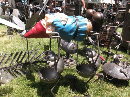 "Sean P. Means  |  The Salt Lake Tribune ""Gnome-be-gones"" cart away a lawn gnome, in the metal sculpture of Salt Lake City artist Fred Conlon, on display at the Utah Arts Festival."