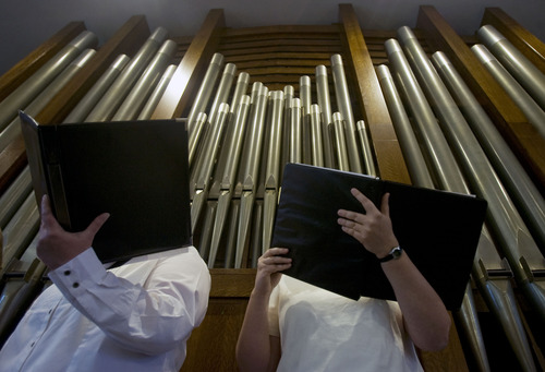 Kim Raff  |  The Salt Lake Tribune (left) Lina Barkey and Sarah Maland, members of the choir of St. Ambrose Catholic Church, sing a hymn as the newly installed Roper Memorial Pipe Organ is played in the sanctuary during Easter Sunday Mass in Salt Lake City on March 31, 2013.