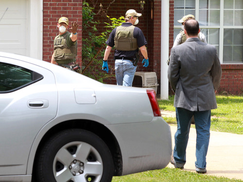 An FBI agent stops homeowner Everett Dutschke from approaching his home Tuesday, April 23, 2013, in Tupelo, Miss., as they search his home in connection with the sending of poisoned letters to President Barack Obama and others last week. Paul Kevin Curtis, the man charged with sending the letters, was released from jail Tuesday on bond, while FBI agents returned Dutschke's house where they'd previously searched in connection with the case. (AP Photo/Northeast Mississippi Daily Journal, Thomas Wells) MANDATORY CREDIT
