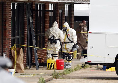 Federal authorities, some in hazmat suits, walk outside the staging area as they search at a small retail space where neighboring business owners said Everett Dutschke used to operate a martial arts studio, in connection with the recent ricin attacks, Wednesday, April 24, 2013 in Tupelo, Miss. No charges have been filed against Dutschke and he hasn't been arrested. (AP Photo/Rogelio V. Solis)