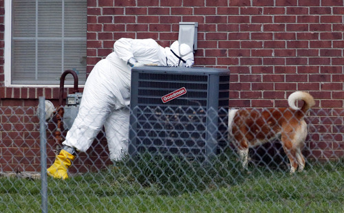 A federal agent wearing a hazmat suits looks behind the air conditioner joined by one of Everett Dutschke's dogs, Tuesday, April 23, 2013 in Tupelo, Miss., in connection with the recent ricin attacks. No charges have been filed against Dutschke and he hasn't been arrested. (AP Photo/Rogelio V. Solis)