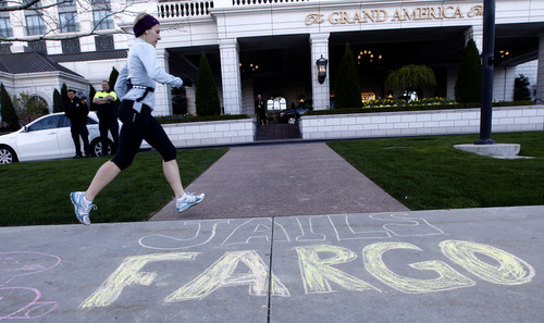 Al Hartmann     The Salt Lake Tribune A runner steps past a chalk message on the sidewalk in front of The Grand America Hotel where 40 protesters, many from the San Francisco-area and associated with ACCE (Alliance of Californians for Community Empowerment), demonstrated Tuesday as Wells Fargo held its annual shareholders meeting. The bank is based in San Francisco. The last two meetings in San Francisco were disrupted by protesters angry at the bank's mortgage foreclosure policies.
