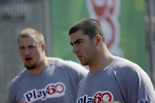 NFL draft prospects Eric Fisher of Central Michigan, right, and Lane Johnson of Oklahoma participate in a youth football clinic in New York, Wednesday, April 24, 2013. (AP Photo/Seth Wenig)