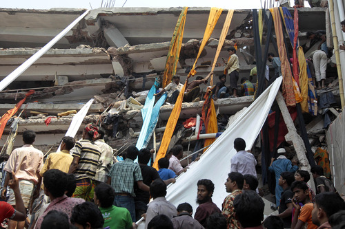 Rescue workers use clothes to bring down survivors and bodies after an eight-story building housing several garment factories collapsed in Savar, near Dhaka, Bangladesh, Wednesday, April 24, 2013. The building collapsed near Bangladesh's capital Wednesday morning, killing dozens of people and trapping many more in the rubble, officials said.  (AP Photo/ A.M. Ahad)