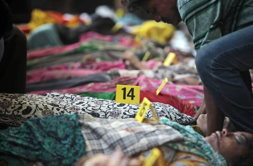 EDS NOTE GRAPHIC CONTENT- Bodies of victims of a building collapse lie numbered in a row in Savar, near Dhaka, Bangladesh, Wednesday, April 24, 2013. An eight-story building housing several garment factories collapsed near Bangladesh's capital on Wednesday, killing dozens of people and trapping many more under a jumbled mess of concrete. Rescuers tried to cut through the debris with earthmovers, drilling machines and their bare hands. (AP Photo/A.M.Ahad)