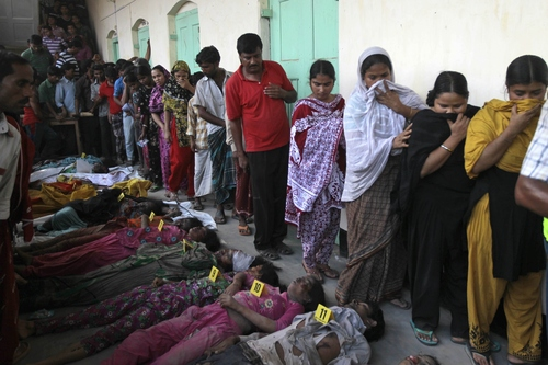 EDS NOTE GRAPHIC CONTENT Bangladeshis walk past bodies of victims to identify relatives who died in a building collapse in Savar, near Dhaka, Bangladesh, Wednesday, April 24, 2013. An eight-story building housing several garment factories collapsed near Bangladesh's capital on Wednesday, killing dozens of people and trapping many more under a jumbled mess of concrete. Rescuers tried to cut through the debris with earthmovers, drilling machines and their bare hands. (AP Photo/A.M.Ahad)