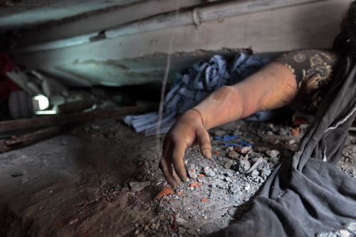 EDITORS NOTE GRAPHIC CONTENT : A victim's body is trapped in rubble after an eight-story building housing several garment factories collapsed in Savar, near Dhaka, Bangladesh, Wednesday, April 24, 2013. Dozens were killed and many more are feared trapped in the rubble. (AP Photo/ A.M. Ahad)