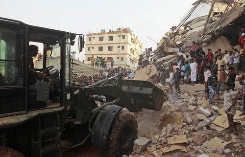 Bangladeshi soldiers use an earthmover during a rescue operation at the site of a building that collapsed  a building collapse in Savar, near Dhaka, Bangladesh, Wednesday, April 24, 2013. An eight-story building housing several garment factories collapsed near Bangladesh's capital on Wednesday, killing dozens of people and trapping many more under a jumbled mess of concrete. Rescuers tried to cut through the debris with earthmovers, drilling machines and their bare hands. (AP Photo/A.M.Ahad)