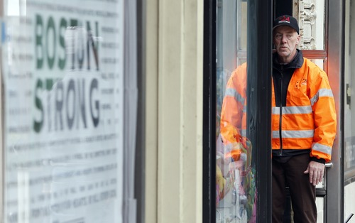 A security guard stands in the entrance to a building on Boylston Street in Boston, Wednesday, April 24, 2013. Businesses opened and traffic was allowed to flow all the way down Boylston Street on Wednesday morning for the first time since two explosions at the Boston Marathon on April 15. (AP Photo/Michael Dwyer)