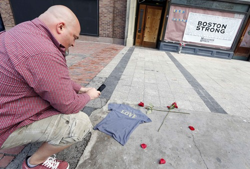Joe Burke, of Haverhill, Mass., places a t-shirt at the spot where the first bomb detonated near the finish line of the Boston Marathon on Boylston Street in Boston, Wednesday, April 24, 2013. Traffic was allowed to flow all the way down Boylston Street on Wednesday morning for the first time since two explosions on April 15. (AP Photo/Michael Dwyer)