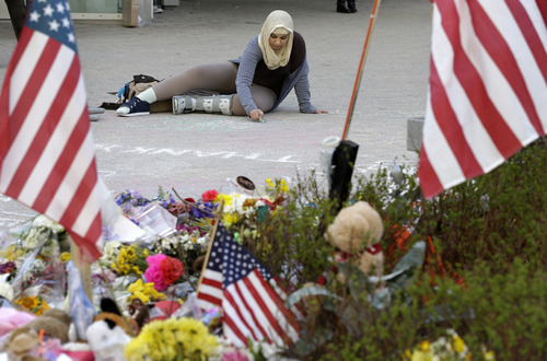 Massachusetts Institute of Technology student Hajar Boughoula of Bizerte, Tunisia, writes a message on the ground with chalk near a makeshift memorial for fallen MIT police officer Sean Collier on the school's campus in Cambridge, Mass., Monday, April 22, 2013. Collier was fatally shot on the MIT campus Thursday, April 18, 2013. Authorities allege that Boston Marathon bombing suspects Tamerlan and Dzhokhar Tsarnaev were responsible. (AP Photo/Steven Senne)