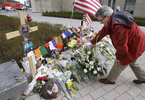 Massachusetts Institute of Technology visiting scientist Tom O'Dwyer, of Arlington, Mass., places flowers at a makeshift memorial to fallen MIT police officer Sean Collier on the school's campus, in Cambridge, Mass., Wednesday, April 24, 2013. Collier was fatally shot on the MIT campus Thursday, April 18, 2013. Authorities allege that the Boston Marathon bombing suspects were responsible. (AP Photo/Steven Senne)
