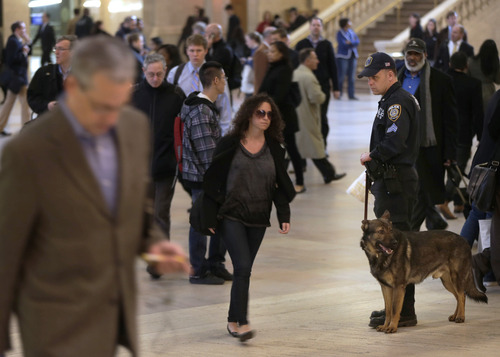 An MTA police officer with a dog patrols in Grand Central Station in New York, Tuesday, April 16, 2013. Police armed with rifles and extra patrol cars were stationed around the city Tuesday as New York remained in a heightened state of alert until more is known about the bombings at the Boston Marathon. (AP Photo/Seth Wenig)