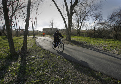 Rick Egan  | The Salt Lake Tribune A bicyclist rides along the Jordan River Trail east of the Utah Cultural Celebration Center at 1355 W. 3100 South. West Valley City plans to build a suspension bridge connecting the trail to the center that will commemorate the pioneers who crossed the river to settle the west side of the Salt Lake Valley.