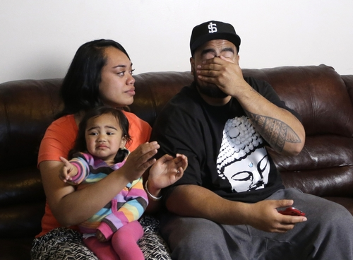 Star Lotulelei, right, reacts as his wife Fuiva holds their daughter Pesatina, 1, after being selected 14th overall by the Carolina Panthers during an NFL football draft party at their home, Thursday, April 25, 2013, in South Jordan, Utah. (AP Photo/Rick Bowmer)