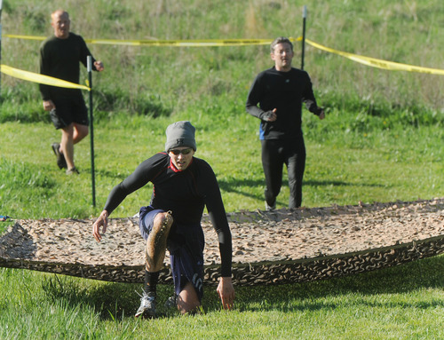 """The Dirty girl 5K Mud Run is Saturday, april 27, in Tooele. In this photo from """"Up, Down and Dirty for a Cure"""" mud run April 20, 2013, at at Diamond Lake Resort near West Louisville, Ky.,Craig Pfifer of Newburgh, Ind., slings water while crawling beneath the net. (AP Photo/The Messenger-Inquirer, John Dunham)"""