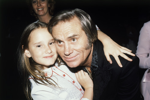 """FILE - In this April 30, 1981 file photo, Country singer George Jones, winner of top male vocalist award at the Academy of Country Music Awards, poses with his daughter Georgette, in Los Angeles, Calif.   Jones, the peerless, hard-living country singer who recorded dozens of hits about good times and regrets and peaked with the heartbreaking classic """"He Stopped Loving Her Today,"""" has died. He was 81. Jones died Friday, April 26, 2013 at Vanderbilt University Medical Center in Nashville after being hospitalized with fever and irregular blood pressure, according to his publicist Kirt Webster.(AP Photo/Nick Ut, file)"""