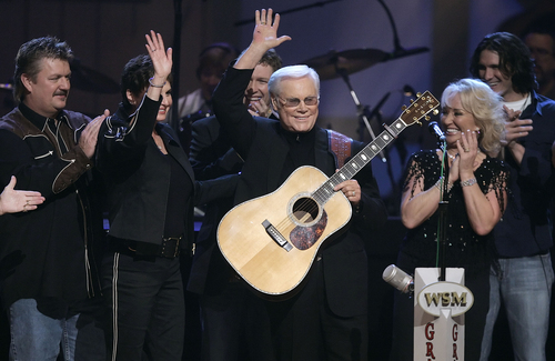 """FILE - In this Sept. 12, 2006 file photo, Country music legend George Jones waves to the crowd during his 75th birthday celebration at the Grand Ole Opry House in Nashville, Tenn., on Tuesday, Sept. 12, 2006. From left are Joe Diffie; Jones' wife, Nancy; Craig Morgan; Jones; Tanya Tucker; and Joe Nichols.   Jones, the peerless, hard-living country singer who recorded dozens of hits about good times and regrets and peaked with the heartbreaking classic """"He Stopped Loving Her Today,"""" has died. He was 81. Jones died Friday, April 26, 2013 at Vanderbilt University Medical Center in Nashville after being hospitalized with fever and irregular blood pressure, according to his publicist Kirt Webster.(AP Photo/Mark Humphrey, file)"""