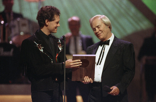 """FILE - In this Sept. 30, 1992 file photo, Country music legend George Jones accepts his Country Music Hall of Fame award from Randy Travis, left, during the Country Music Association Awards show, Nashville, Tenn. Jones, the peerless, hard-living country singer who recorded dozens of hits about good times and regrets and peaked with the heartbreaking classic """"He Stopped Loving Her Today,"""" has died. He was 81. Jones died Friday, April 26, 2013 at Vanderbilt University Medical Center in Nashville after being hospitalized with fever and irregular blood pressure, according to his publicist Kirt Webster. (AP Photo/Mark Humphrey, file)"""