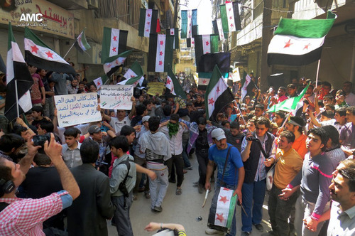 """This citizen journalism image provided by Aleppo Media Center AMC which has been authenticated based on its contents and other AP reporting, shows anti Syrian regime protesters holding banners and waving the Syrian revolutionary flags during a demonstration, in Aleppo, Syria, Friday, April 26, 2013. Araboc on banners read: """"we call upon the Free Syrian Army brigades and the Mujahedeen to stop the military convoy in the city of al-Safira,"""" left, and """"all what Kerry has is the laughing cow cheese .""""(AP Photo/Aleppo Media Center AMC)"""