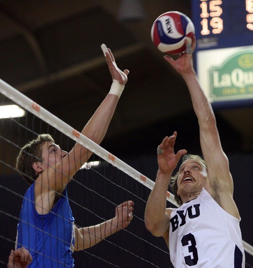 Kim Raff  |  The Salt Lake Tribune (right) BYU player Ryan Boyce tips the ball over the net as (left) UCLA player Robart Page defends in the semifinals of the MPSF Volleyball Tournament at the Smith Fieldhouse in Prove on April 25, 2013. BYU went on to win the match 3-2 after being down two sets.