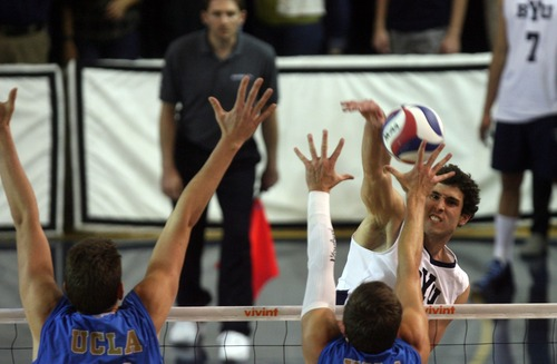 Kim Raff  |  The Salt Lake Tribune (right) BYU player Josue Rivera spikes the ball over the hands of UCLA players (left) Trent Kersten and (middle) Dane Worley during the semifinals of the MPSF Volleyball Tournament at the Smith Fieldhouse in Prove on April 25, 2013.  BYU went on to win the match 3-2 after trailing UCLA by two sets.