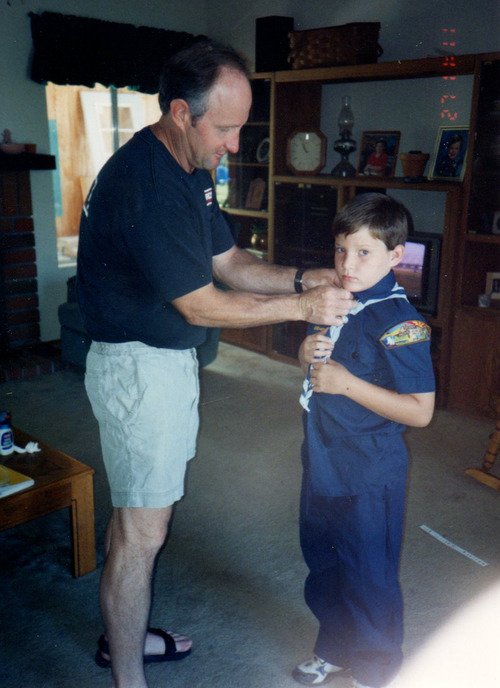 "In this circa 1997 photo provided by the family, Timothy O'Brien adjusts the Cub Scout uniform of his son Ian at their home in Santee, Calif. In early 2013, Ian O'Brien, 23, wrote an opinion piece tied to the Boy Scout debate and his own experience in the Scouts when he was growing up in the San Diego area. ""To put it simply: Being a boy is supposed to look one way, and you get punished when it doesn't,"" O'Brien wrote in the piece, which appeared in The Advocate, a national magazine for the gay, lesbian, bisexual and transgender communities. (AP Photo/Ian O'Brien)"