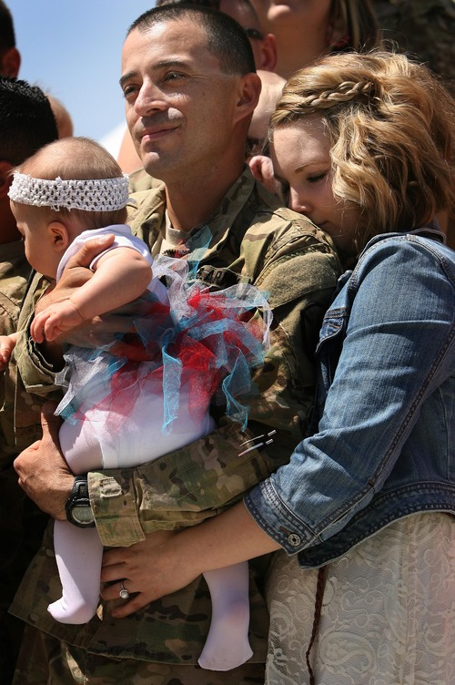 Leah Hogsten  |  The Salt Lake Tribune Bethany Perea hugs her husband, Spc. Matt Perea, holding his 8-month-old daughter, Sienna, for the first time. Twenty-seven babies, 23 single births and two sets of twins were born to wives of returning soldiers of the Utah National Guard's 624th Engineer Company, 1457th Engineer Battalion,Thursday, April 25, 2013, during their 10-month deployment to Afghanistan.