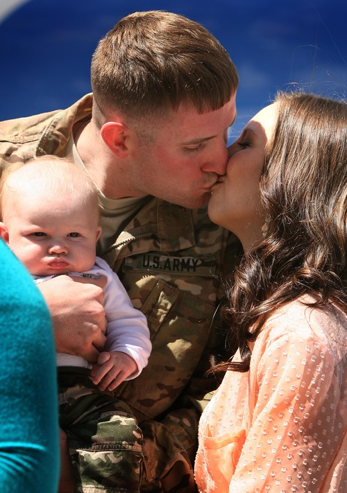 Leah Hogsten  |  The Salt Lake Tribune After stepping off the plane and seeing his 3-month-old son, Karter, for the first time, Sgt. Brian Skelton proposed to his girlfriend, Ashley Blake. Twenty-seven babies, including two sets of twins, were born to wives and partners of returning soldiers of the Utah National Guard's 624th Engineer Company, 1457th Engineer Battalion,Thursday, April 25, 2013, during their 10-month deployment to Afghanistan.