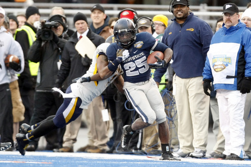 Chris Detrick  |  The Salt Lake Tribune Utah State Aggies running back Kerwynn Williams (25) is forced out of bounds by Toledo Rockets defensive back Cheatham Norrils (11) during the second quarter of the Famous Idaho Potato Bowl at Bronco Stadium Saturday December 15, 2012.  At the end of the first half the Aggies were winning, 10-6.