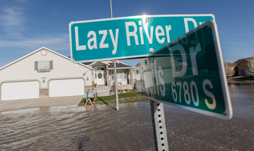 Trent Nelson  |  The Salt Lake Tribune Flood waters from the breached North Jordan Canal engulf Lazy River Drive, Saturday, April 27, 2013 in Murray.