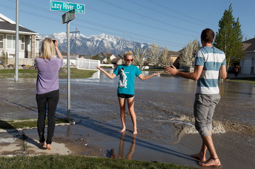Trent Nelson  |  The Salt Lake Tribune Shandi Schoeneman, center, poses for a photo on Lazy River Drive after a canal breach sent water flooding into a Murray neighborhood Saturday, April 27, 2013.