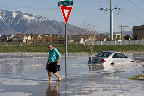 Trent Nelson  |  The Salt Lake Tribune David Gomez makes his way across the street after a canal breach sent water flooding into a Murray neighborhood Saturday, April 27, 2013.