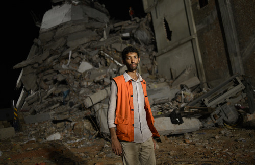Saiful Islam Nasar poses in front of the rubble of a building collapse in Savar, near Dhaka, Bangladesh Monday April 2013. Nasar, a mechanical engineer is one of hordes of volunteers who came to Savar to help with the rescue effort. They get no funding, have no training and buy their supplies themselves. They have featured largely in efforts to save those who were crushed in the worst disaster to hit Bangladesh's $20 billion a year garment industry.(AP Photo/Ismail Ferdous)