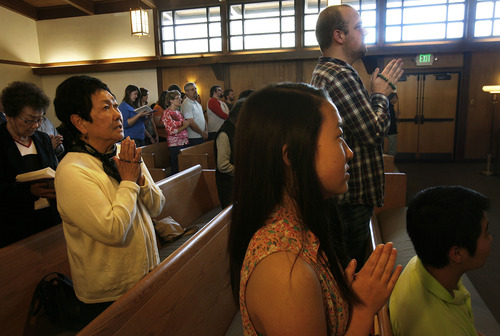 Scott Sommerdorf   |  The Salt Lake Tribune People pray during services at the Salt Lake Buddhist Temple, Sunday, April 21, 2013.