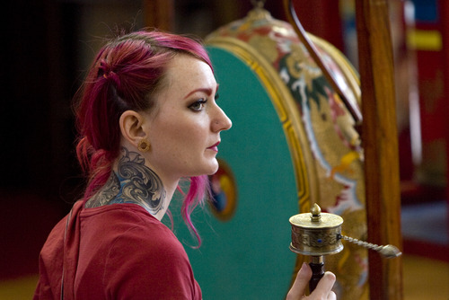 Kim Raff  |  The Salt Lake Tribune Andrea Hansen uses a hand held prayer wheel during a ceremony at the Urgyen Samten Ling Buddhist temple in Salt Lake City on April 21, 2013. The building was once a Mormon ward and a gothic nightclub before it was renovated and became a Buddhist temple.