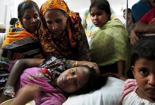 Merina, a survivor of the garment factory building collapse, is comforted by family members in hospital on Saturday April 27, 2013 in Savar, near Dhaka, Bangladesh. Merina was trapped under rubble for three days, surviving with nothing to eat and only a few sips of water. The building collapse was the worst disaster to hit Bangladesh's $20 billion a year garment industry.(AP Photo/Gillian Wong)