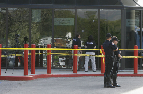 Francisco Kjolseth  |  The Salt Lake Tribune Forensics investigators overlook several bullet holes seen on the glass of the lobby to the West Valley City Police Department. Police were investigating the scene of a shooting where one person was shot in a confrontation inside the lobby on Monday morning.