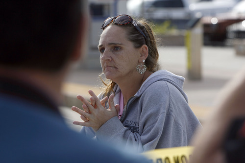 Francisco Kjolseth  |  The Salt Lake Tribune Bonnie Barkhimer of West Valley, clearly agitated over her experience of being on a TRAX train at the West Valley Central station when bullets started flying out of the WVC Police station next door, is held to tell police what she saw. Police were investigating the scene of a shooting at the West Valley City Police Department where one person was shot in a confrontation inside the lobby on Monday morning.