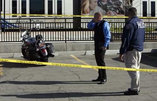 Francisco Kjolseth  |  The Salt Lake Tribune Police examine a motorcyle possibly belonging to a man shot during a confrontation Monday in the lobby of the West Valley Police Department.