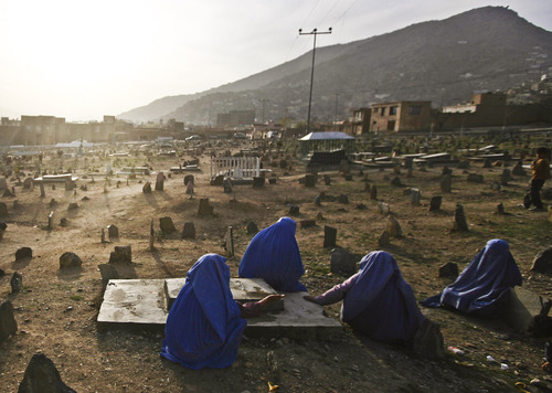 FILE - In this Saturday, March 20, 2010 file photo, Afghan women offer prayers at the grave of their relative in a grave yard in the outskirts of Kabul, Afghanistan. As the country braces for next year's presidential election and the planned withdrawal of most foreign combat troops by the end of 2014, the panel urges the U.S. government and its allies to work harder to promote religious rights in the war-torn nation. (AP Photo/Rafiq Maqbool, File)