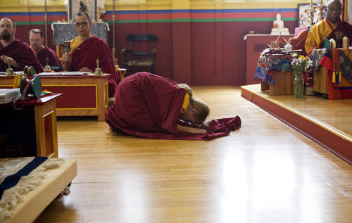 Kim Raff  |  The Salt Lake Tribune Davin Fackrell bows in front of the shrine during a ceremony at the Urgyen Samten Ling Buddhist temple in Salt Lake City on April 21, 2013. The building was once a Mormon ward and a gothic nightclub before it was renovated and became a Buddhist temple.