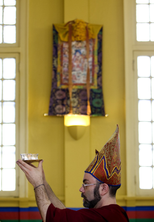 Kim Raff  |  The Salt Lake Tribune Chopon Jared Kee stands in front of the shrine holding candles during a ceremony at the Urgyen Samten Ling Buddhist temple in Salt Lake City on April 21, 2013. The building was once a Mormon ward and a gothic nightclub before it was renovated and became a Buddhist temple.